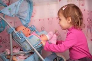 תינוקת עם בובה בעגלה