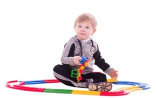 תינוק משחק עם רכבת צעצוע