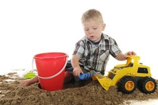 ילד בן 4 משחק עם צעצועים בחול
